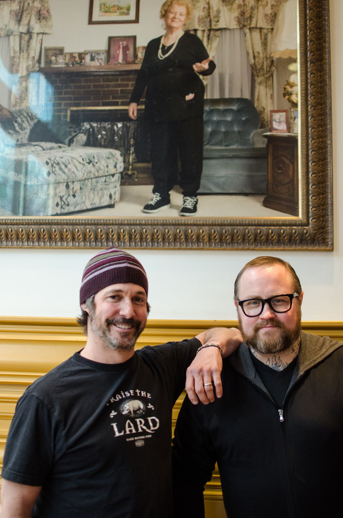 """Two men stand under a painted portrait of an Italian grandma. One man is wearing a black t-shirt that says """"Praise the Lard"""" and the other is wearing black, thick-rimmed glasses."""
