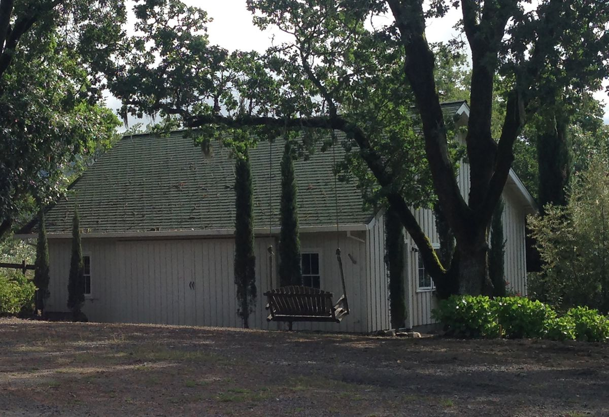 Gray barn with a swing hanging on a tree.