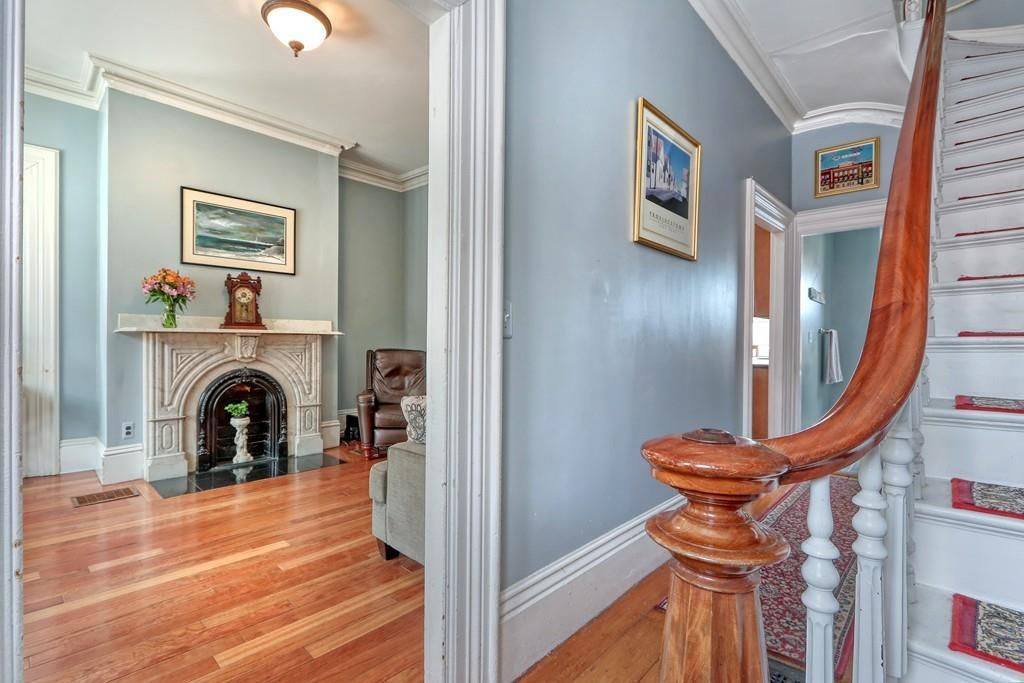 An entry foyer with a close-up on the banister of the main stairs, and a fireplace visible in the living room to the side.