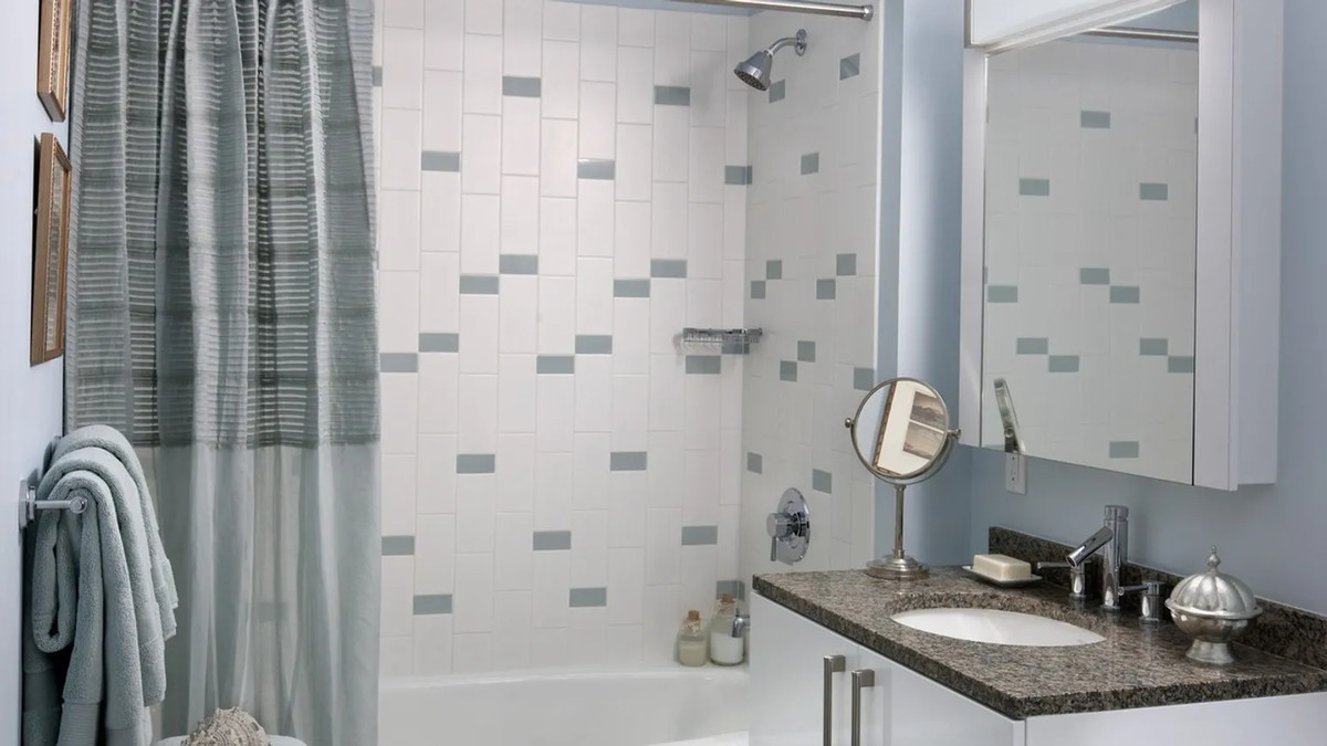 A bathroom with white and light blue tiles.