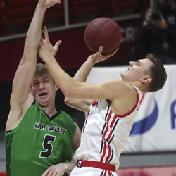 Utah Utes guard Pelle Larsson (3) shoots over UVU Wolverines forward Tim Fuller (5) during a game at the Huntsman Center in Salt Lake City on Tuesday, Dec. 15, 2020.