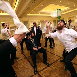 Nochum Greenwald balances an empty bottle on his nose during Chaya Zippel and Rabbi Mendy Cohen's traditional Hasidic wedding at the Grand America Hotel in Salt Lake City on Monday, Sept. 12, 2016.