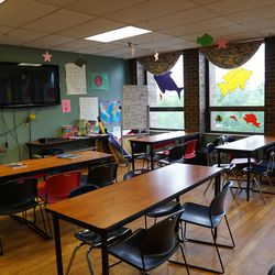 Cardboard cutouts hang from the ceiling in a room filled with desks and chairs. | Provided by Heartland Alliance