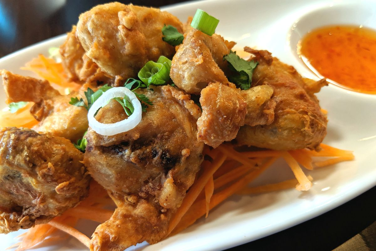 Fried pieces of chicken sit on a bed of carrot strips on a white oval plate with a side bowl of a sweet chile sauce.