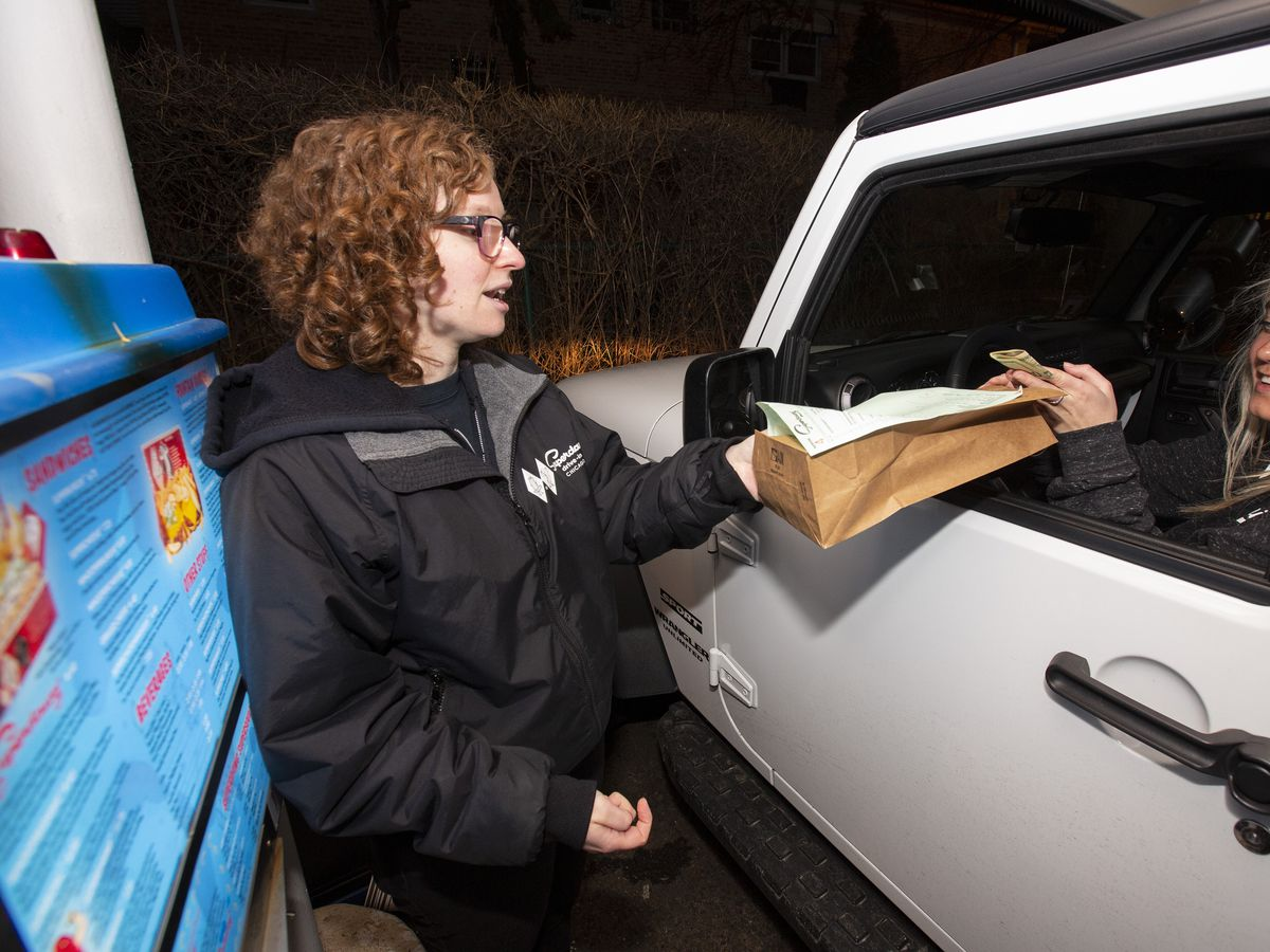 A person with curly red hair wearing glasses hands a bag of food to a person sitting in an SUV.
