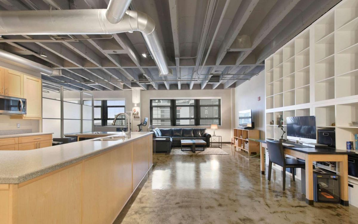 Long view of loft with kitchen to the left, desk and shelving on the right, and couch and table in the background.