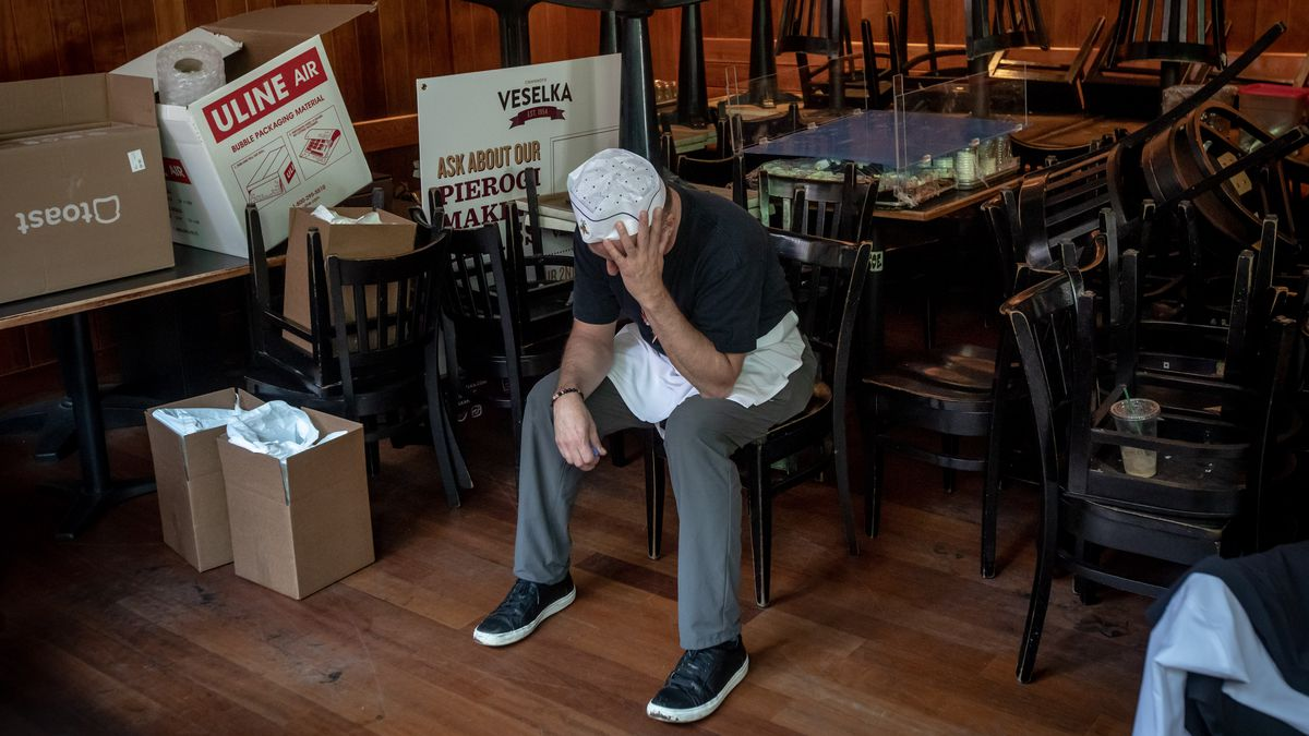 Veselka owner Jason Birchard sits in his dining room adjacent empty chairs, tables, and boxes