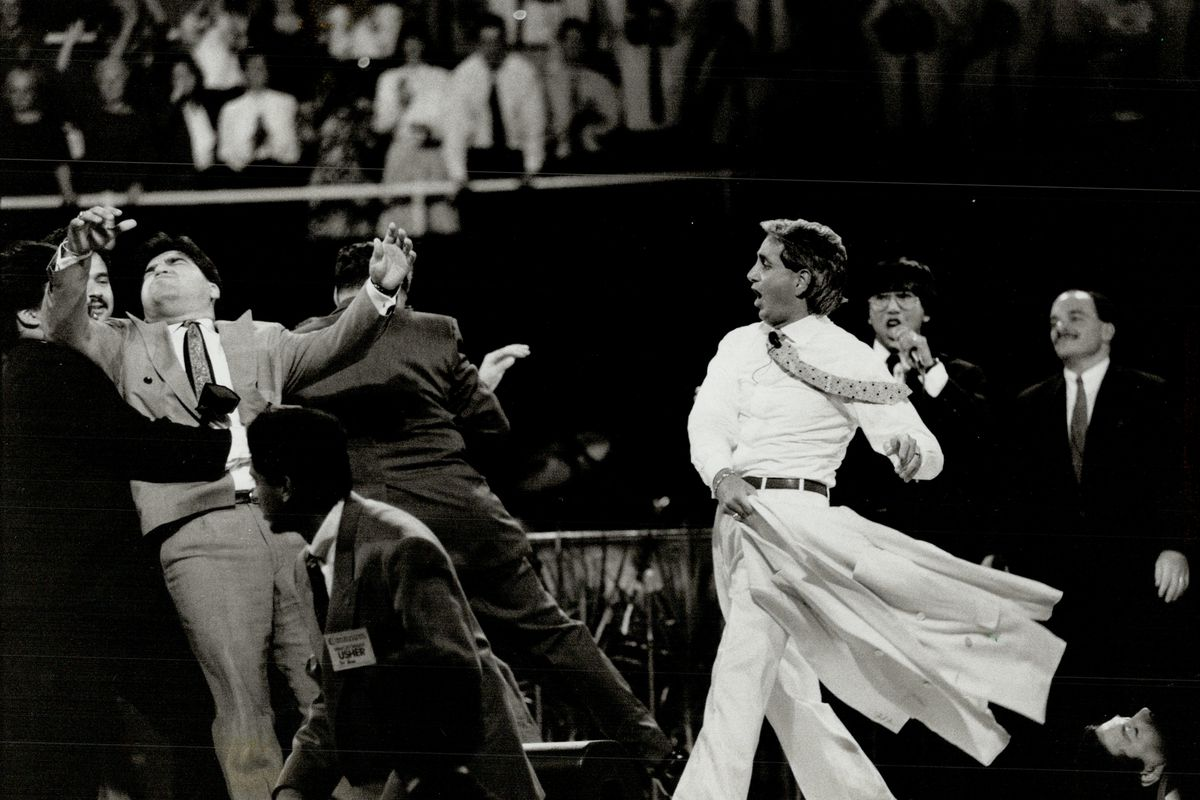 Benny Hinn: At left; and above; during Maple Leaf Gardens performance where he waved his coat about;