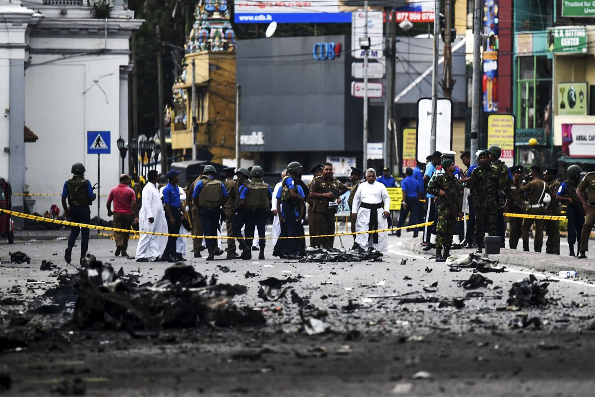 Sri Lankan security personnel inspect the debris of a car after it exploded near St. Anthony's Church.