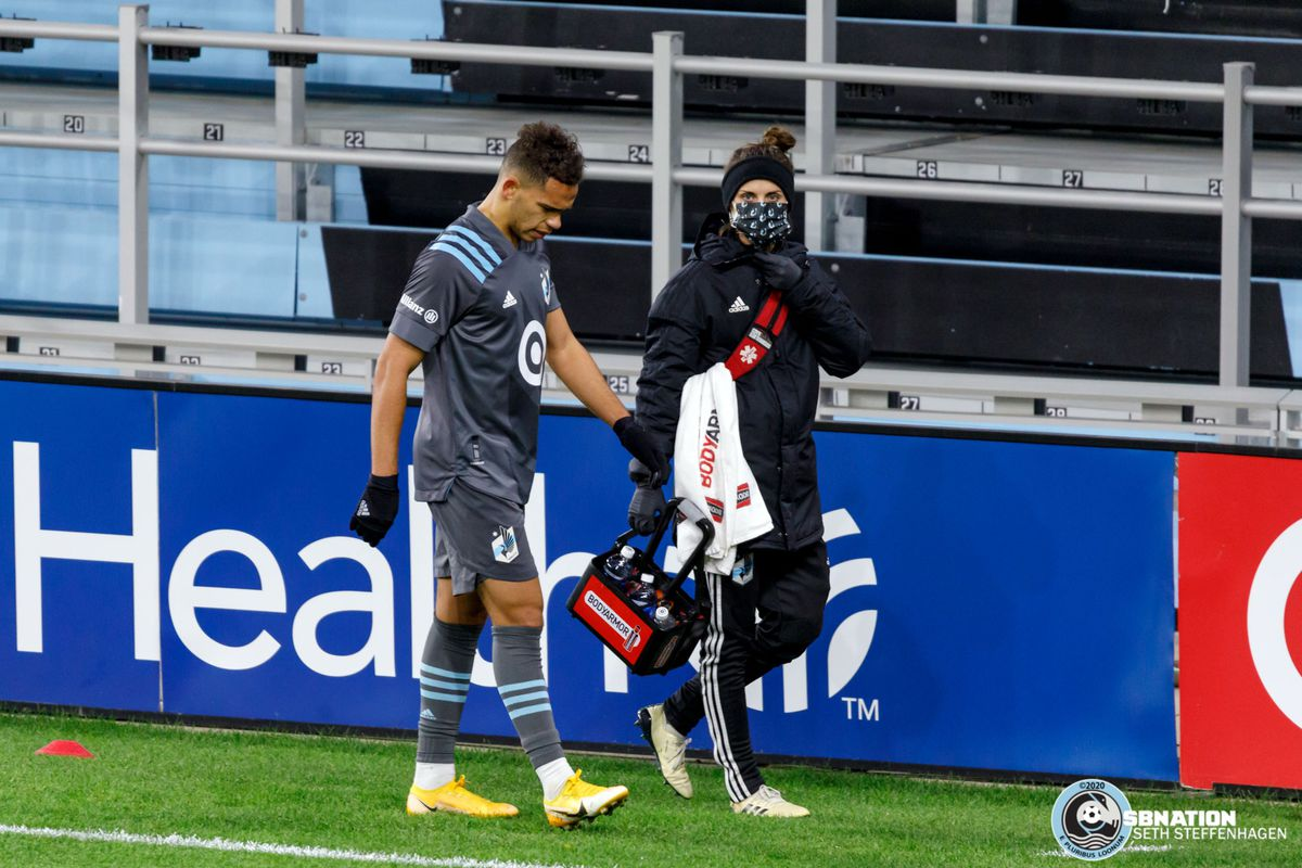 October 18, 2020 - Saint Paul, Minnesota, United States - Minnesota United midfielder Hassani Dotson (31) walks off injured with head athletic trainer Stacey Hardin during the match against the Houston Dynamo at Allianz Field.