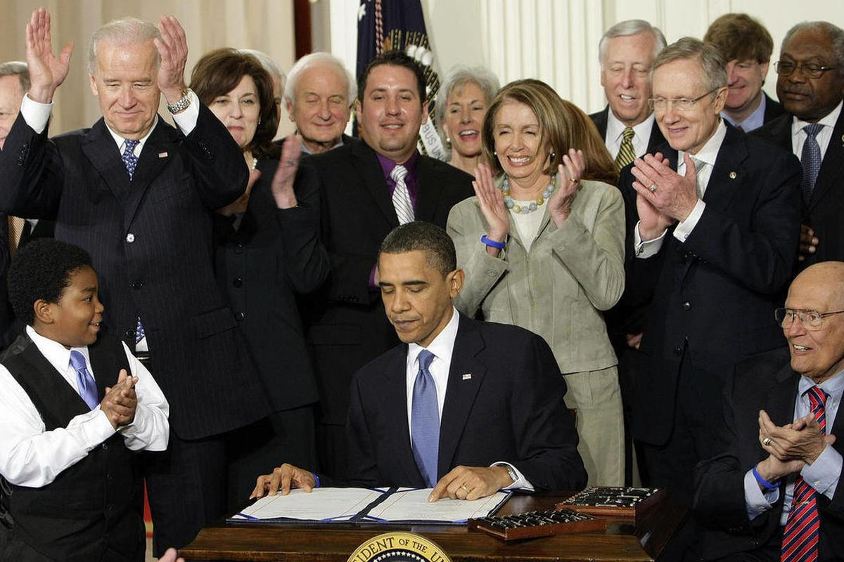 FILE - In this March 23, 2010, file photo, participants applaud in the East Room of the White House in Washington, Tuesday, March 23, 2010, as President Barack Obama, flanked by Macelas Owens of Seattle, left, and Rep. John Dingell, D-Mich., right, signs