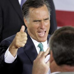 Republican presidential candidate, former Massachusetts Gov. Mitt Romney poses for a photo for a supporter at a campaign stop in Charlotte, N.C., Wednesday, April 18, 2012.