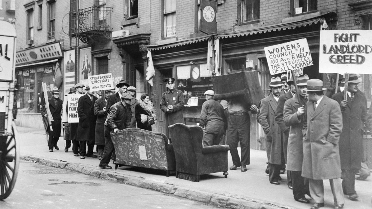 A black and white photo of a crowd in Manhattan protesting an eviction as workers carry tenants' furniture out from an apartment building to the curb.