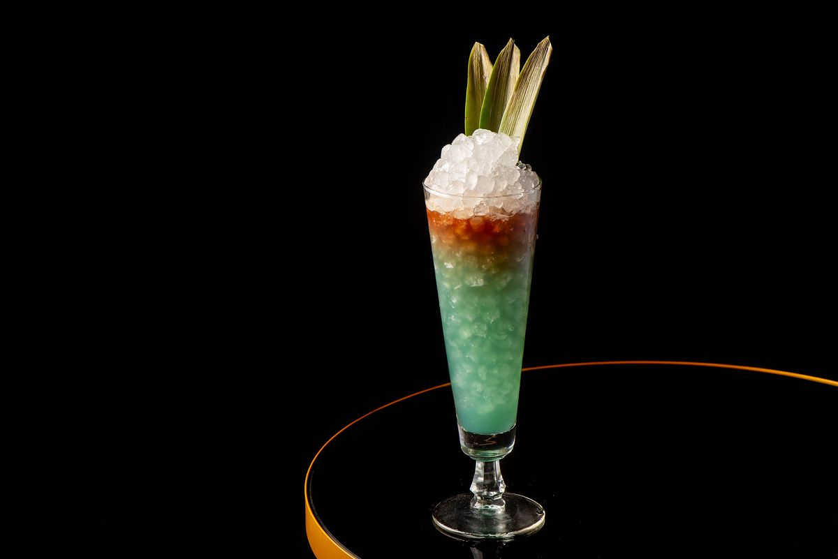Blue Hawaiian with rum, chartreuse, coconut, pineapple, and blue Curacao in a tall glass with crushed ice and pineapple leaf garnish.