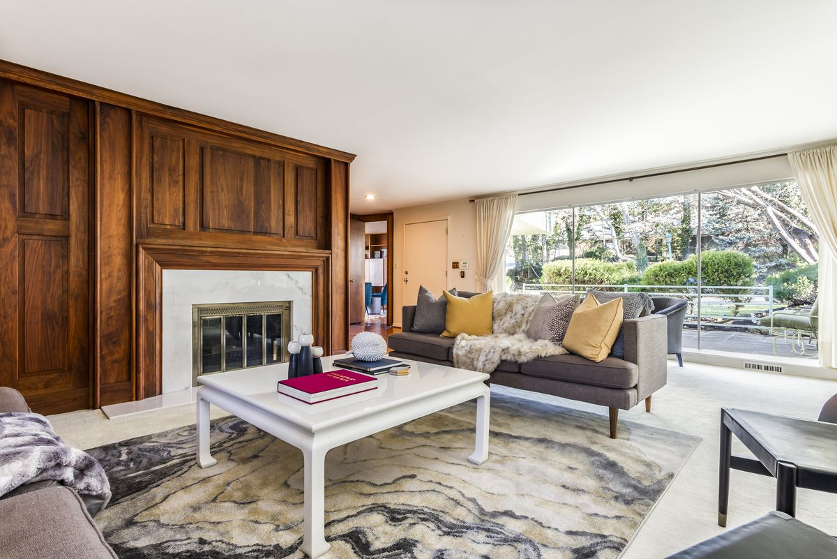 A living room has a fireplace, white coffee table, and contemporary couches and rugs.