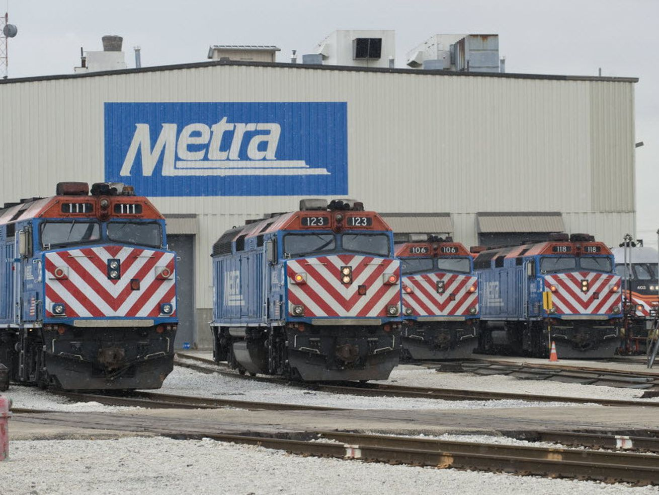 Metra trains parked outside a train barn.