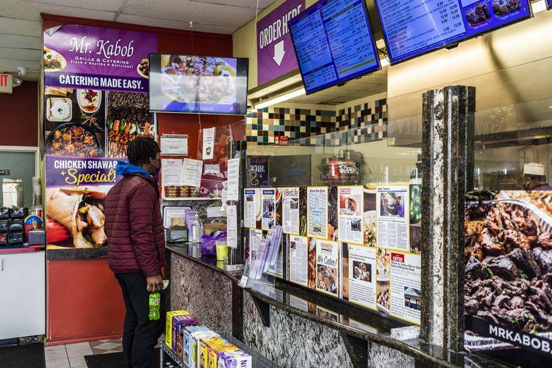 Man considers the menu while standing at a counter; a digital menu board hangs above.