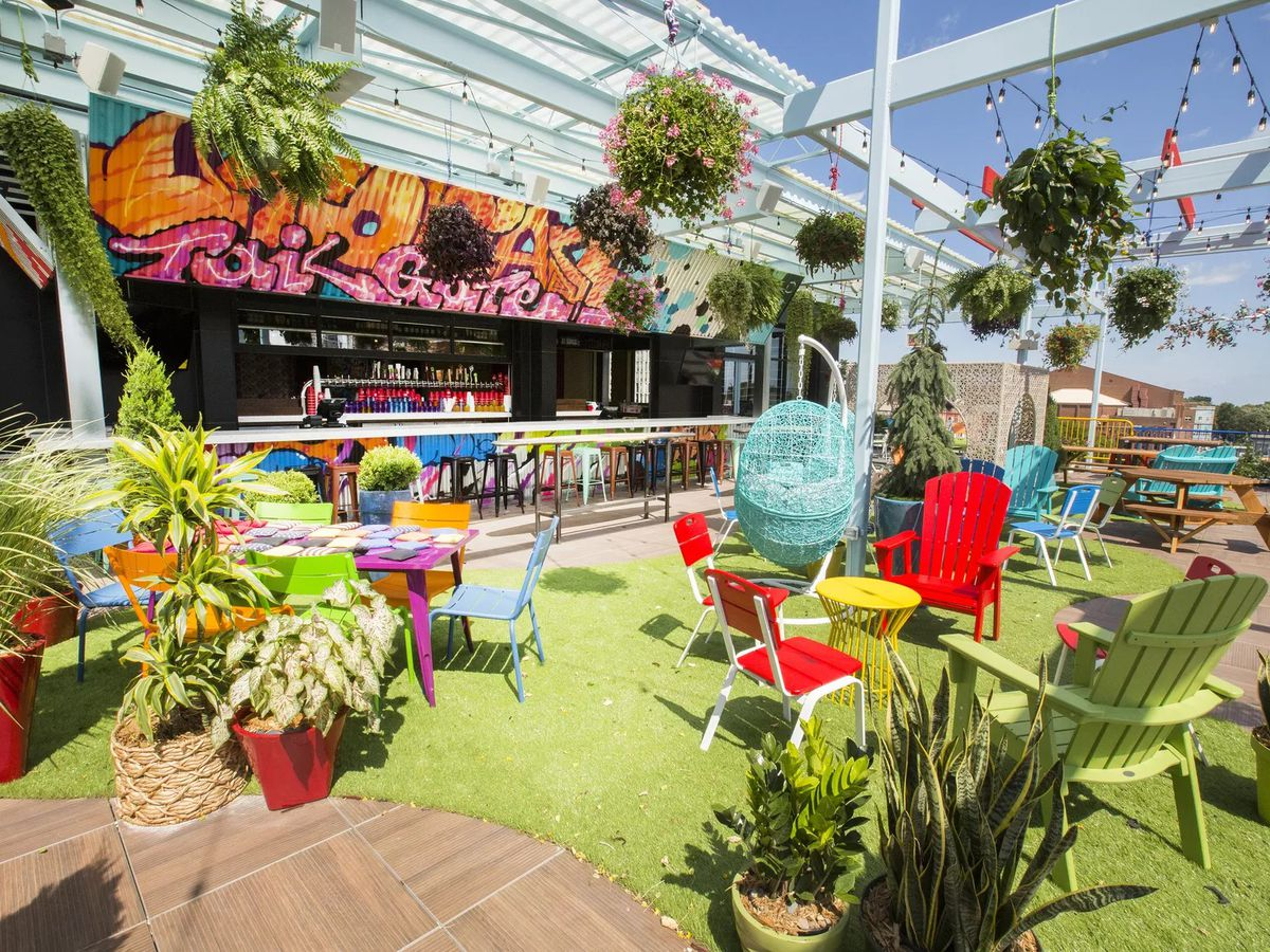 A rooftop patio covered in astroturf with colorful lawn chairs, plants, and a bar.
