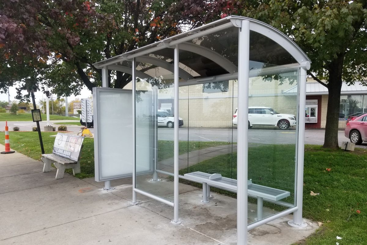 A metal bus shelter with a narrow bench and curved roof. There's a solar panel on top.