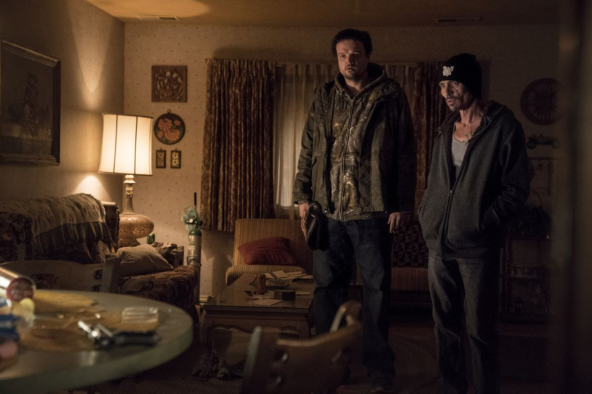 Looking stunned, Badger (Jones) and Pete (Baker) stand in the middle of their living room.