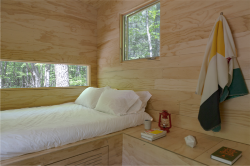 The interior of a wooden cabin. There is a bed, a shelf, and a hook on the wall which holds a colorful towel.