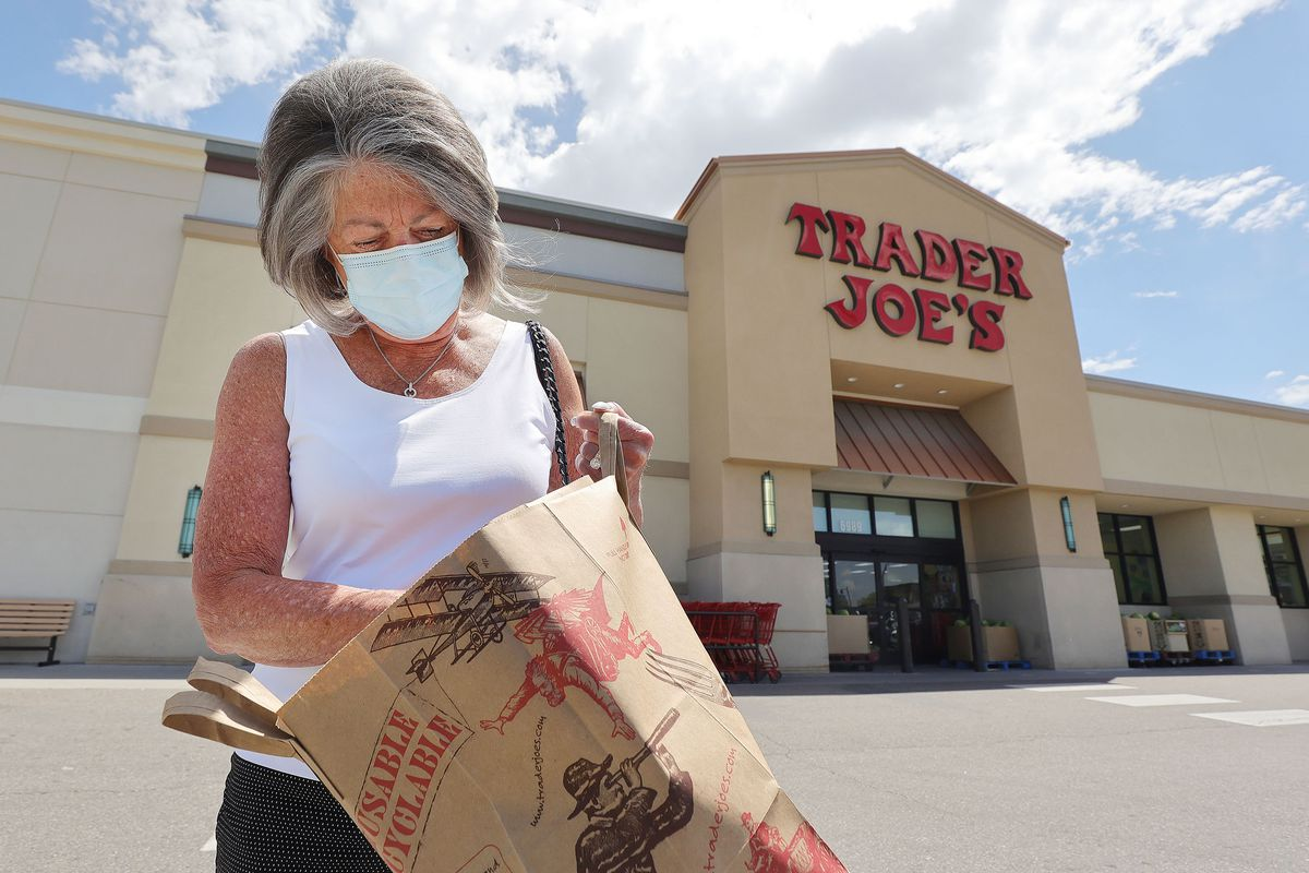 A woman walks with a mask outside of Trader Joe's in Utah.