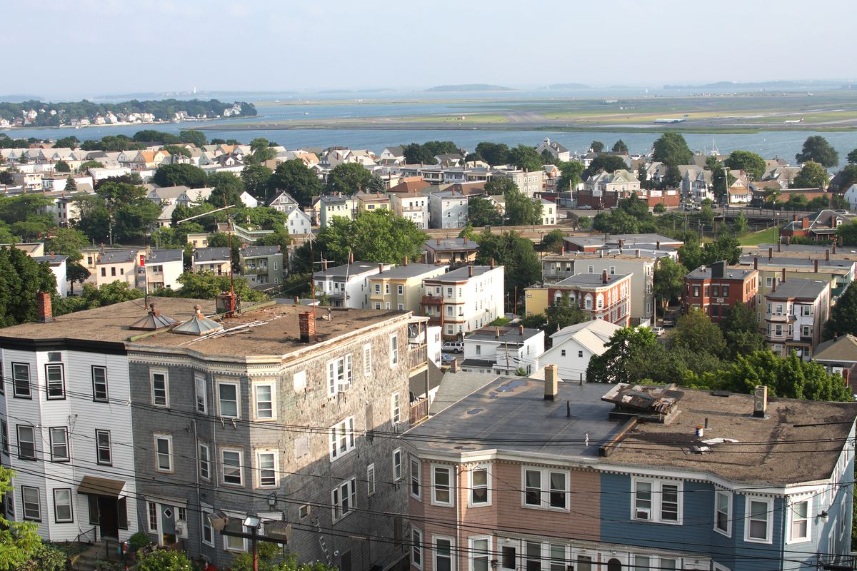 An aerial view over a Boston neighborhood, filled with row homes + town homes, and the water behind.