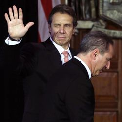 New York Gov. Andrew Cuomo, left, winks and waves as he and Howard Glaser, New York state director of operations, leave the Red Room after a cabinet meeting at the Capitol on Thursday, Sept. 27, 2012, in Albany, N.Y. Cuomo is calling a summit to boost the beer and wine industries in New York just months after a similar effort began to try to make New York the nations largest producer of Greek-style yogurt.