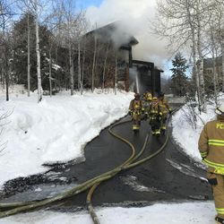Firefighters battle a house fire in Summit Park on Wednesday, Jan. 13, 2016.