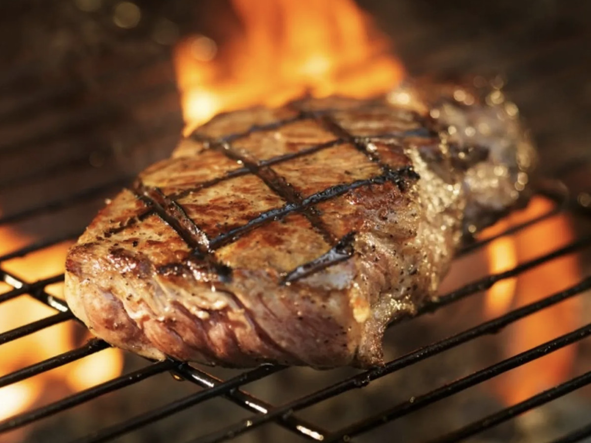 A hunk of steak on the grill with flames leaping up in the background