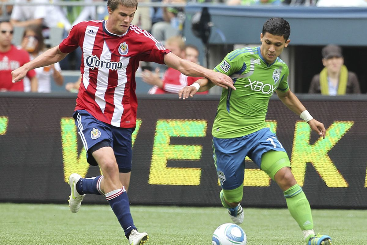 SEATTLE - AUGUST 13:  Fredy Montero #17 of the Seattle Sounders FC battles Justin Braun #17 of Chivas USA at CenturyLink Field on August 13, 2011 in Seattle, Washington. (Photo by Otto Greule Jr/Getty Images)