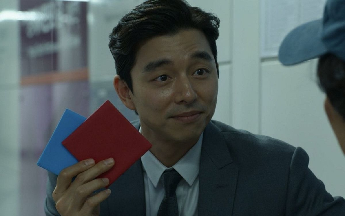 The salesman (Gong yoo) holding two folded pieces of paper in Squid Game.