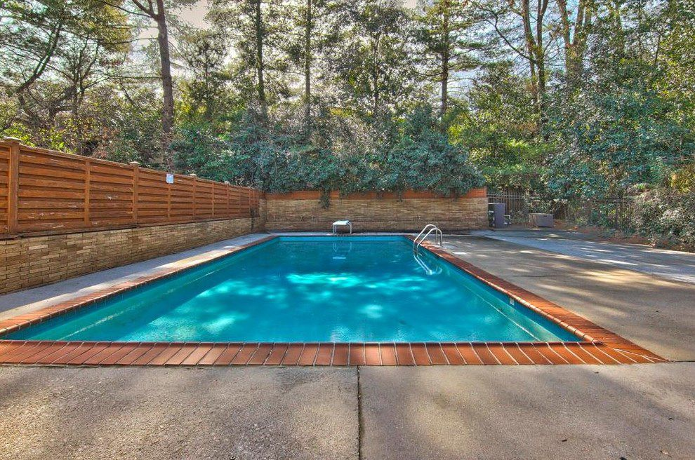 A large blue pool surrounded by a diving board and patio.