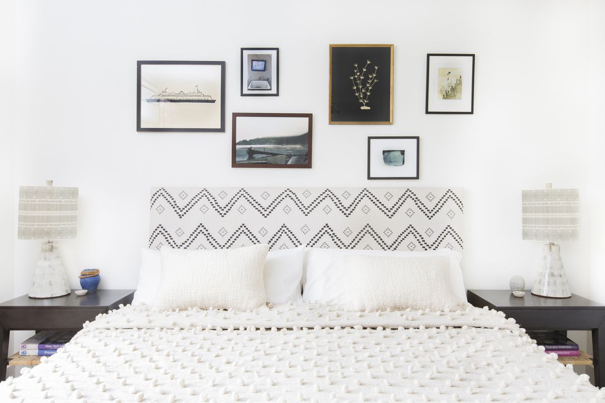 A white bedroom has a black-and-white fabric on the headboard. A collection of small framed art hangs over the bed.