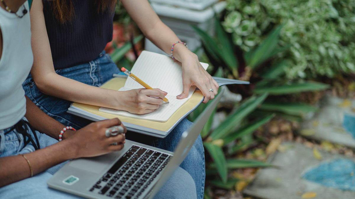 Two adolescent students sit next to each other on a park bench and collaborate on school work