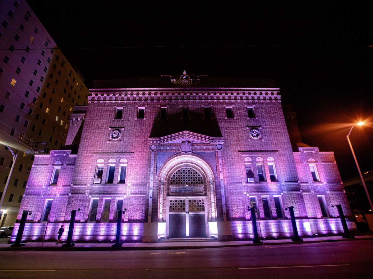 The exterior of 1137 St. Charles Avenue in New Orleans. The facade is white and illuminated in purple light. There is a fence in front and an arched doorway.