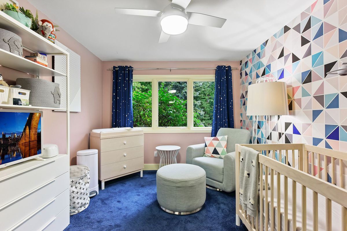A nursery with a crib, chair, and a pink and blue geometric accent wall.