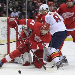 Detroit Red Wings defenseman Brad Stuart (23) deflects the puck away from Florida Panthers left wing Wojtek Wolski (8), of Poland, during the second period of an NHL hockey game in Detroit, Sunday, April 1, 2012.