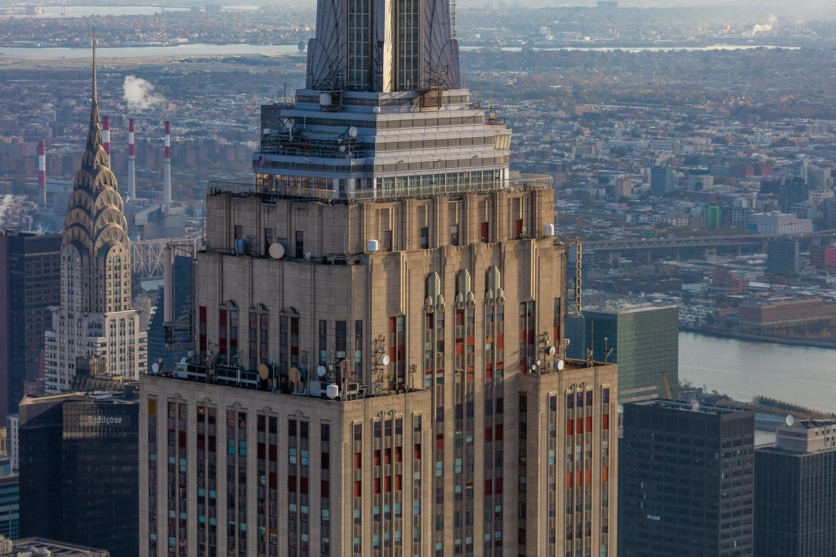 The top of a large skyscraper, with many windows and brass ornamentation on the exterior. There are other skyscrapers surrounding it, and a large river behind it.
