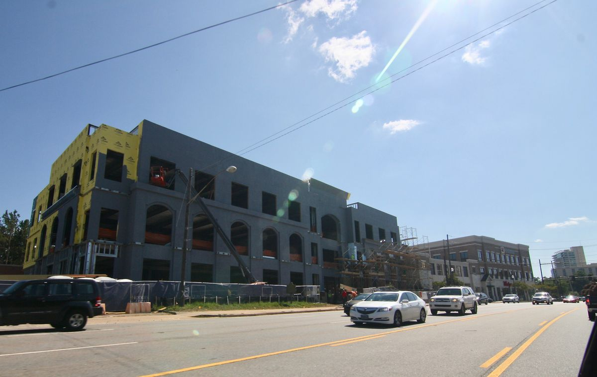 A gray building under construction with a road and cars at right.