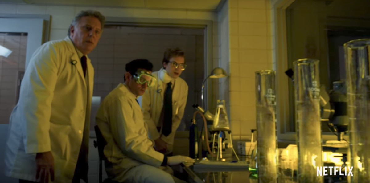 Group of three scientists standing in a lab, with one wearing glasses on the right