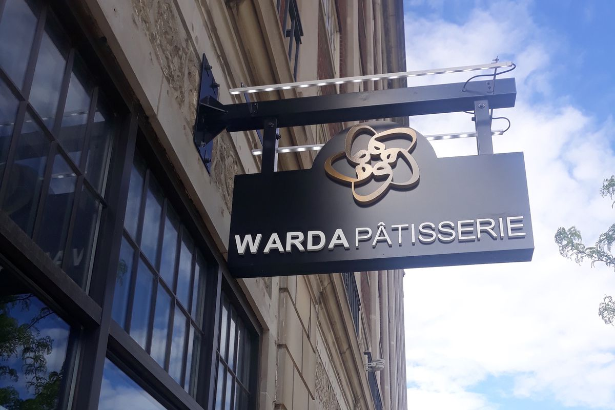 """A """"Warda Pâtisserie"""" sign sits atop a brick building with covered glass doors."""