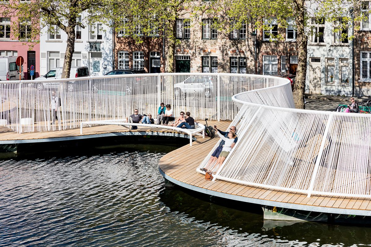 A floating pavilion is being proposed for a canal in Bruges, Belgium, which would snake along the shoreline and offer passersby an opportunity to walk along on the water or simply stop and relax. The pavilion itself would be make of wooden planks, while r