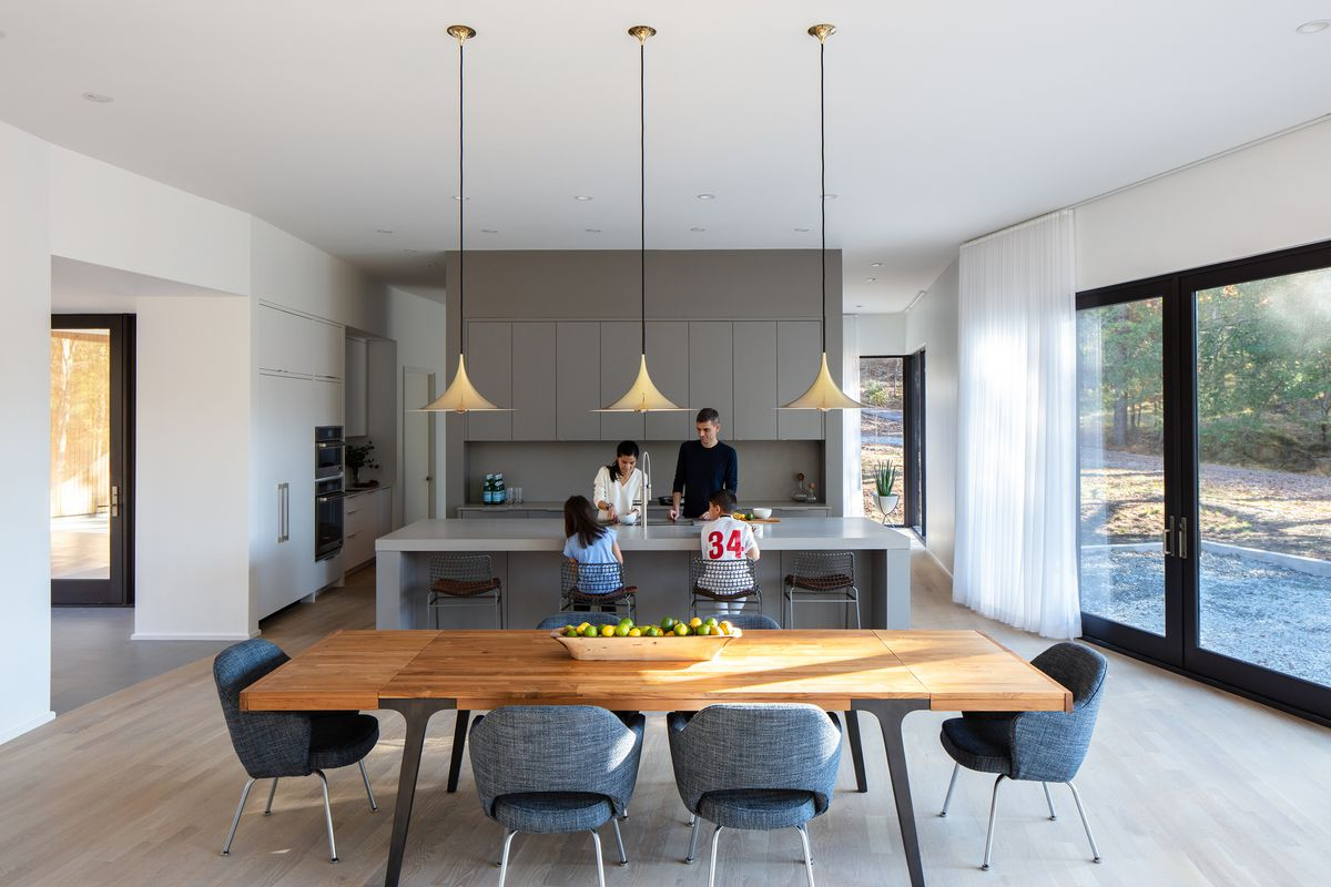 An open kitchen/dining room features a long teak wood table with vintage gray armchairs and three brass pendants above. An all-kitchen kitchen with an island is in the background.