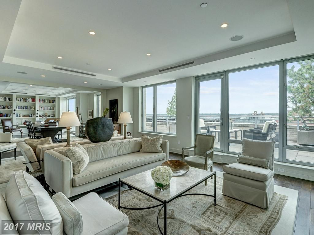 A living area with couches, chairs, a table, and floor to ceiling windows.