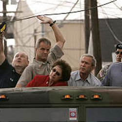 Vice Adm. Thad Allen, left, and an unidentified man lift a downed power line Monday as they tour downtown New Orleans with Louisiana Gov. Kathleen Blanco, President Bush, Lt. Gen. Russ Honore and New Orleans Mayor Ray Nagin. It was Bush's third visit since the storm hit.
