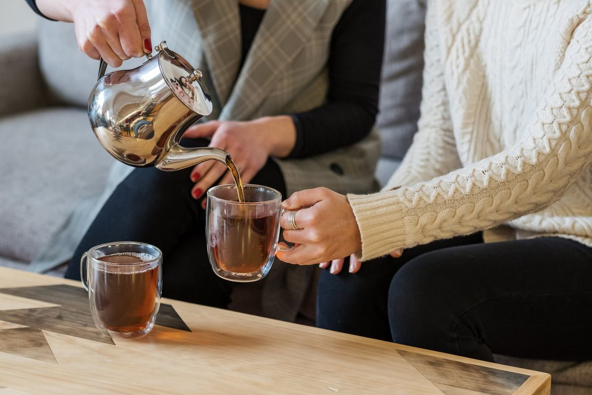 Two people sit next to each other and pour tea int glass mugs at Townshend Tea, also known as Brew Dr.