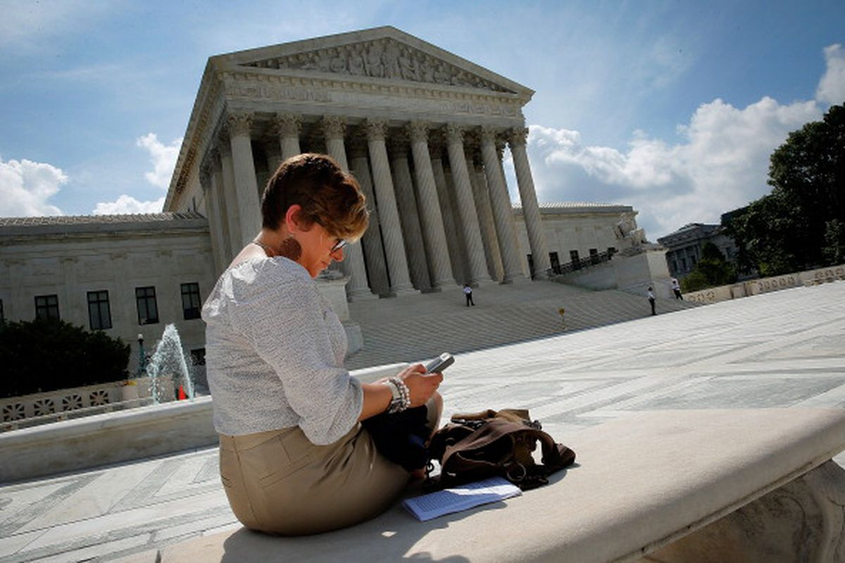 Kirsten Luna from Holland, Michigan, uses her smartphone outside the U.S. Supreme Court after a major ruling on cell phone privacy by the court June 25, 2014 in Washington, DC.