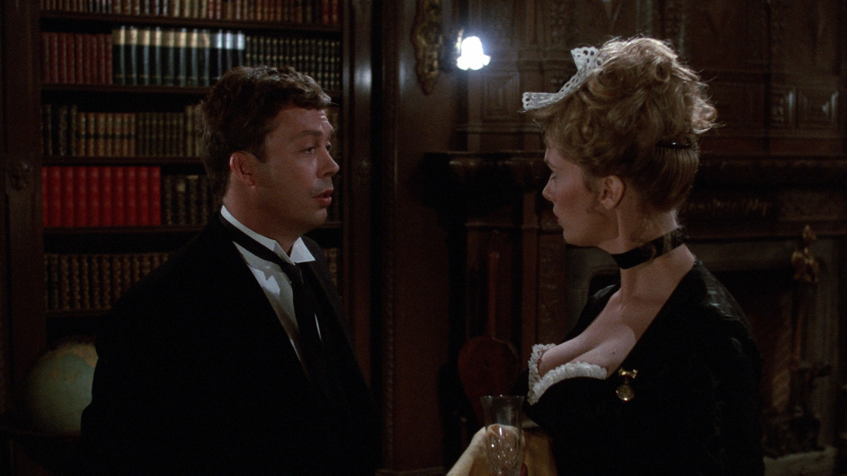 Tim Curry and Colleen Camp, as the butler and maid in Clue, talk before their guests arrive