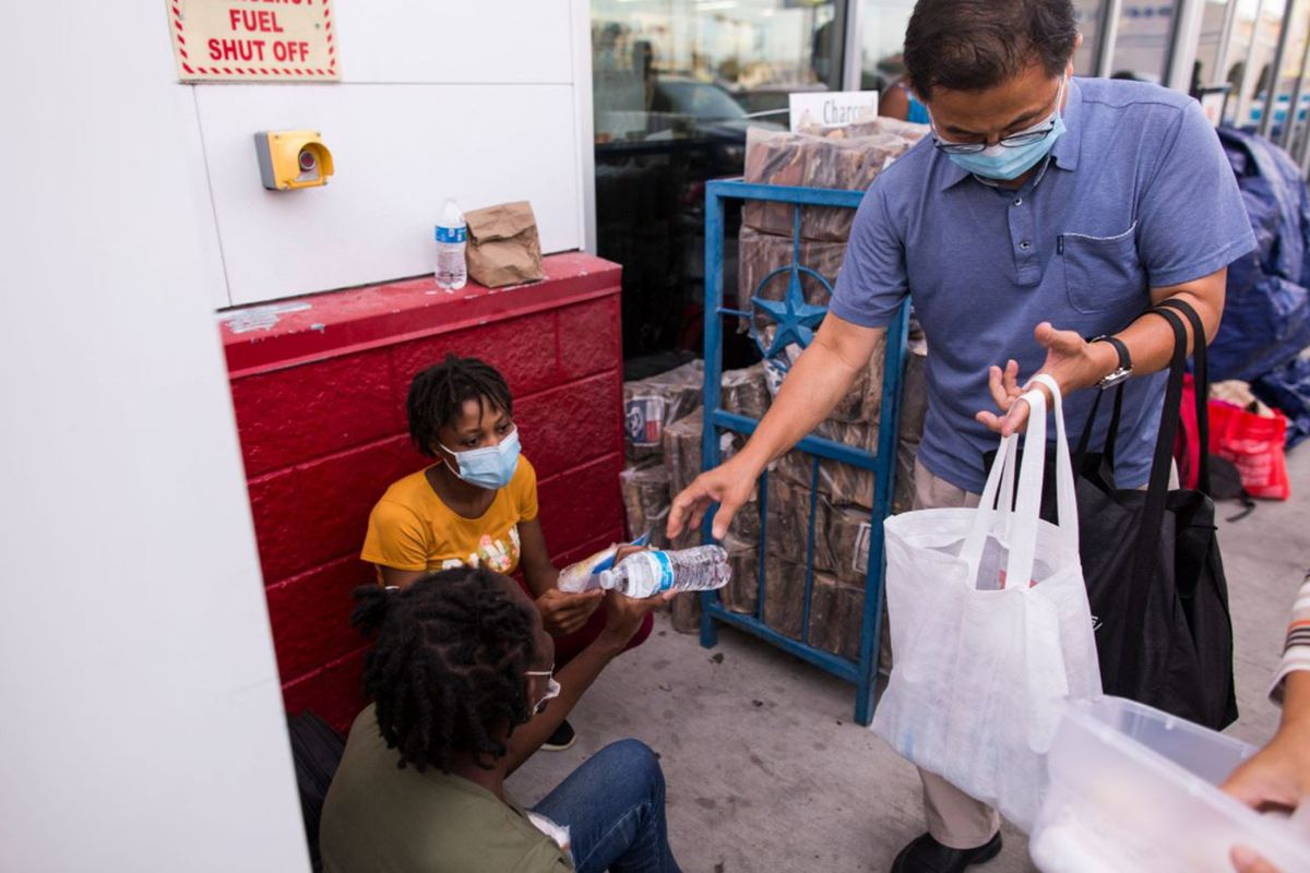 Pastor Greg Yeum hands out bottled water to Haitian migrants at a Del Rio, Texas, gas station, Sept. 22, 2021.